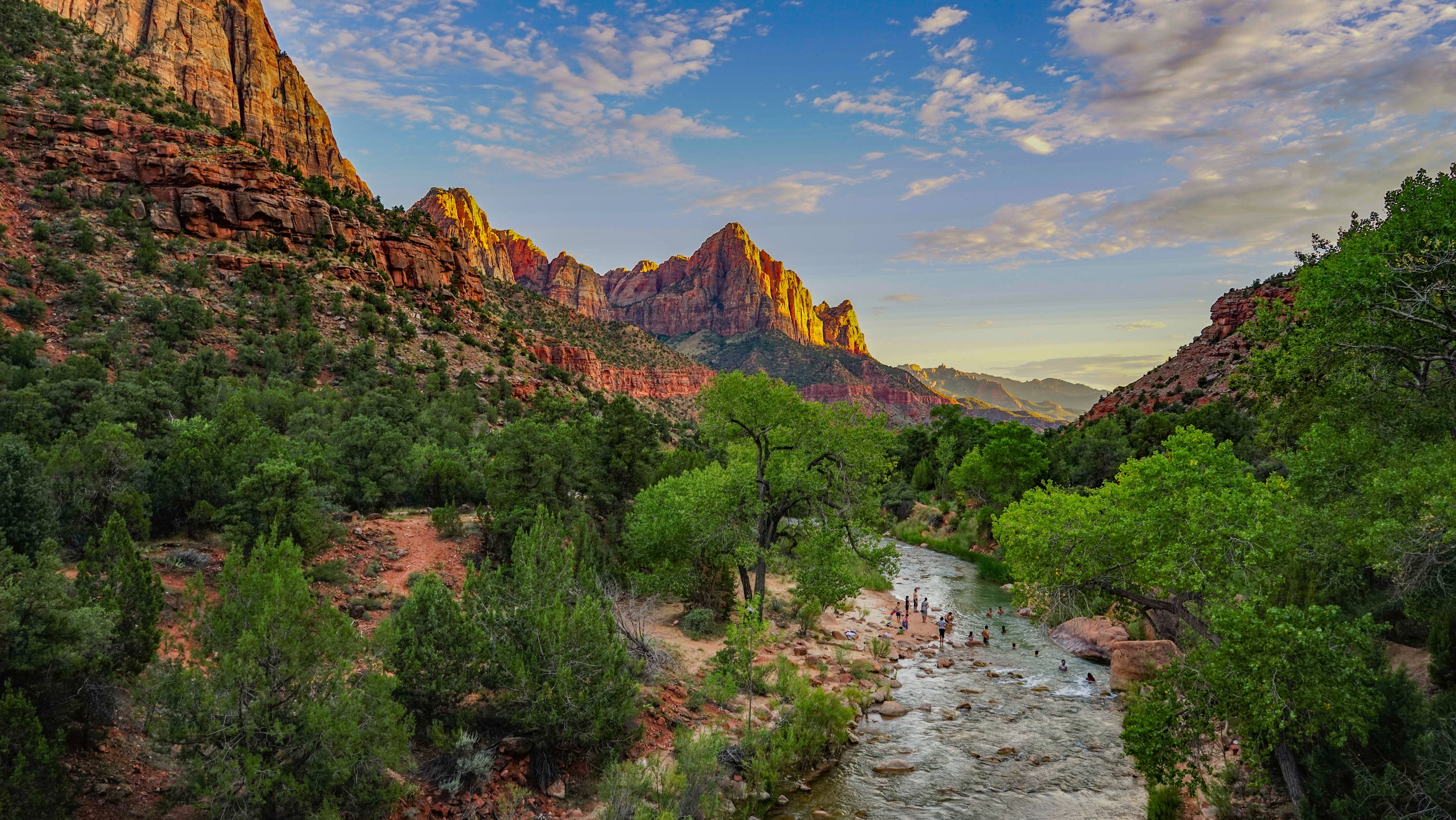 National Parks near Las Vegas, Nevada: People swimming in Virgin River with lush green trees on either side and red standstone formations in distance in Zion National Park.