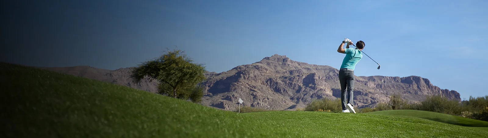 Man on swinging on a golf course in the mountains