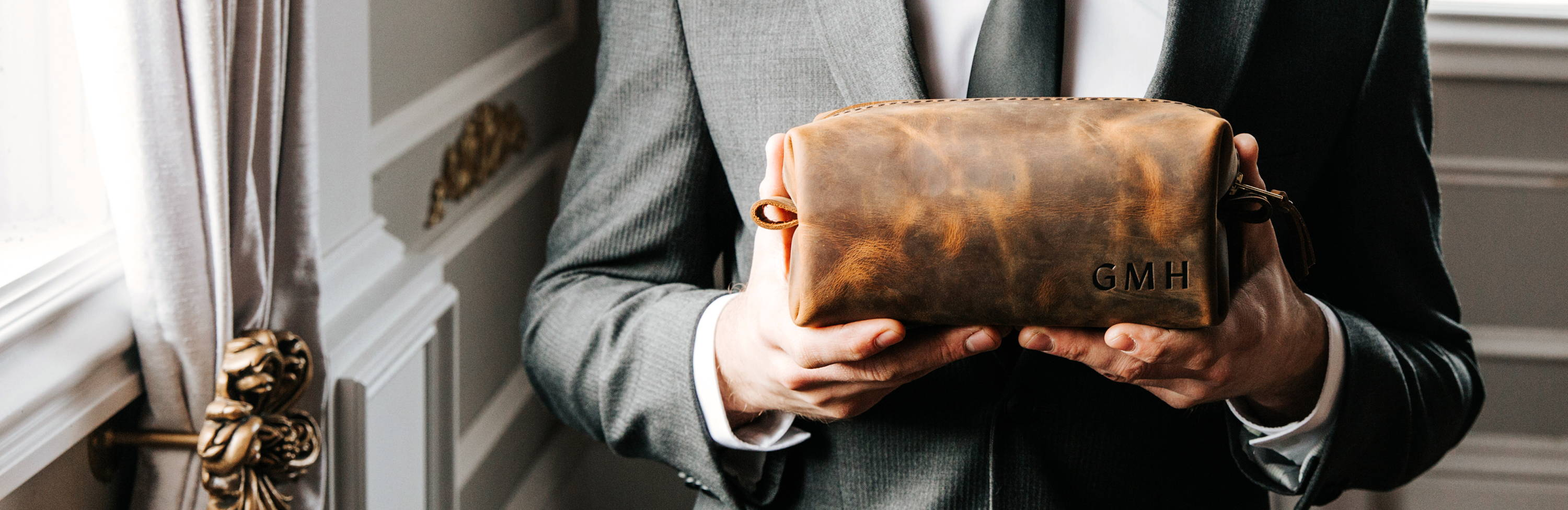 suited man holding a personalized dopp kit bag