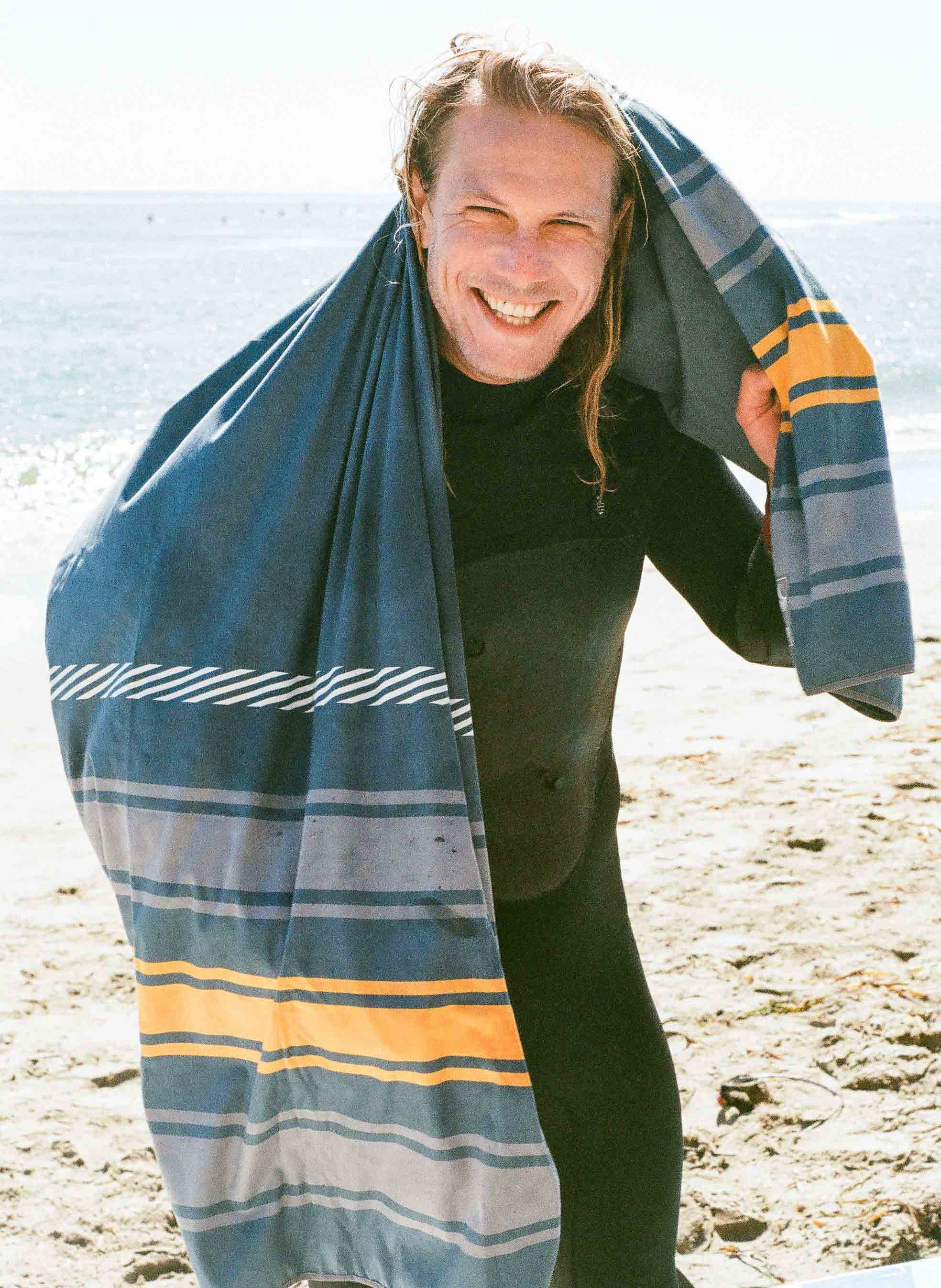 Smiling surfer with wetsuit on and drying off with High Fives Shammy