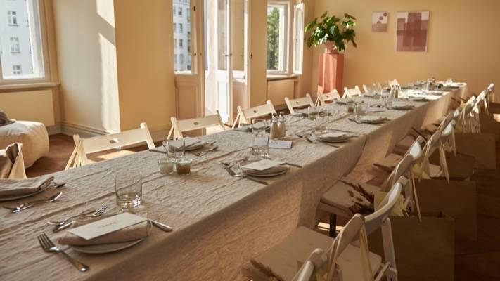 Eine lange Tafel, die mit Leinentischdecke und Tellern eingedeckt ist