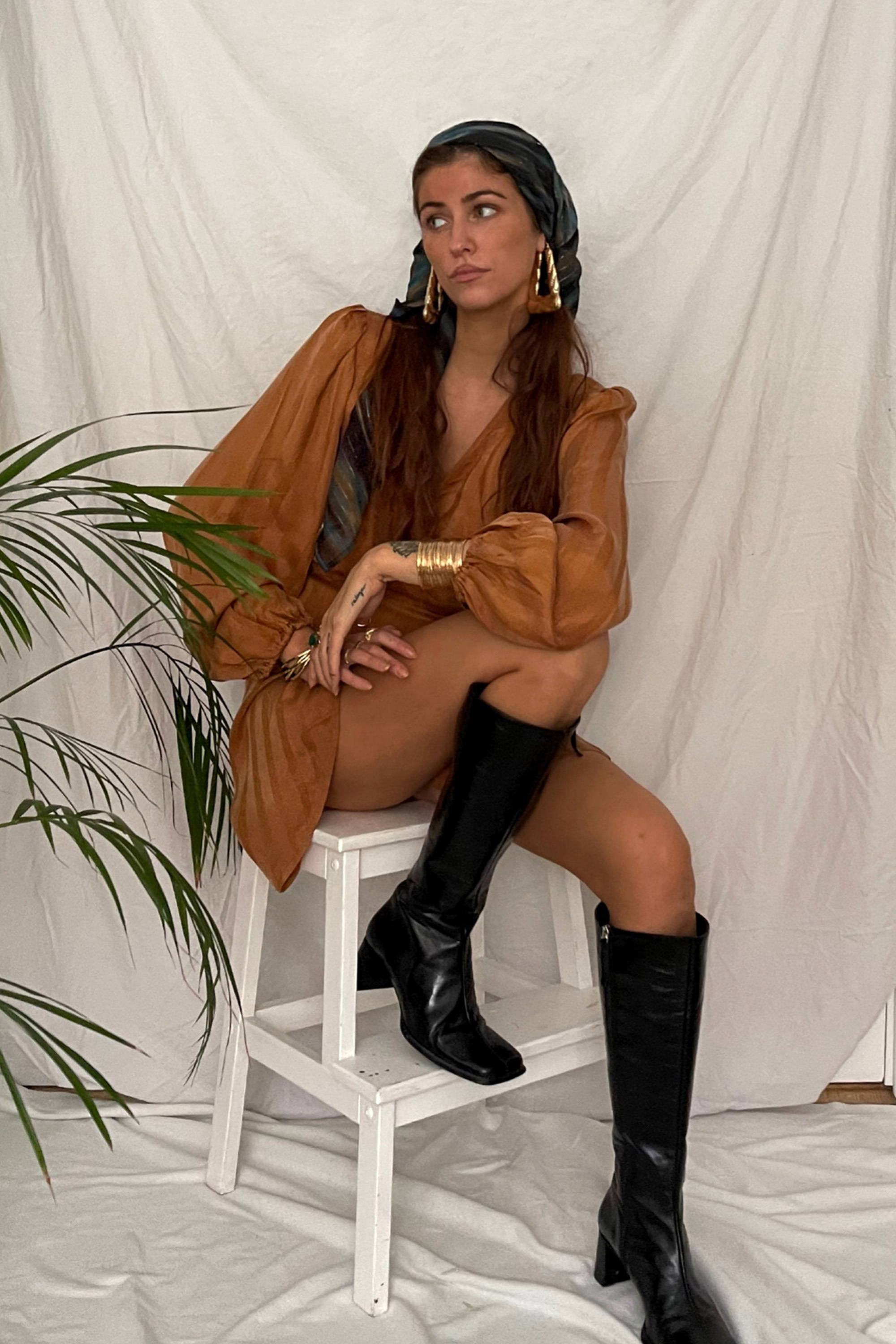 Girl sitting on stool wearing long black boots and wrap mini dress boho style in brown.
