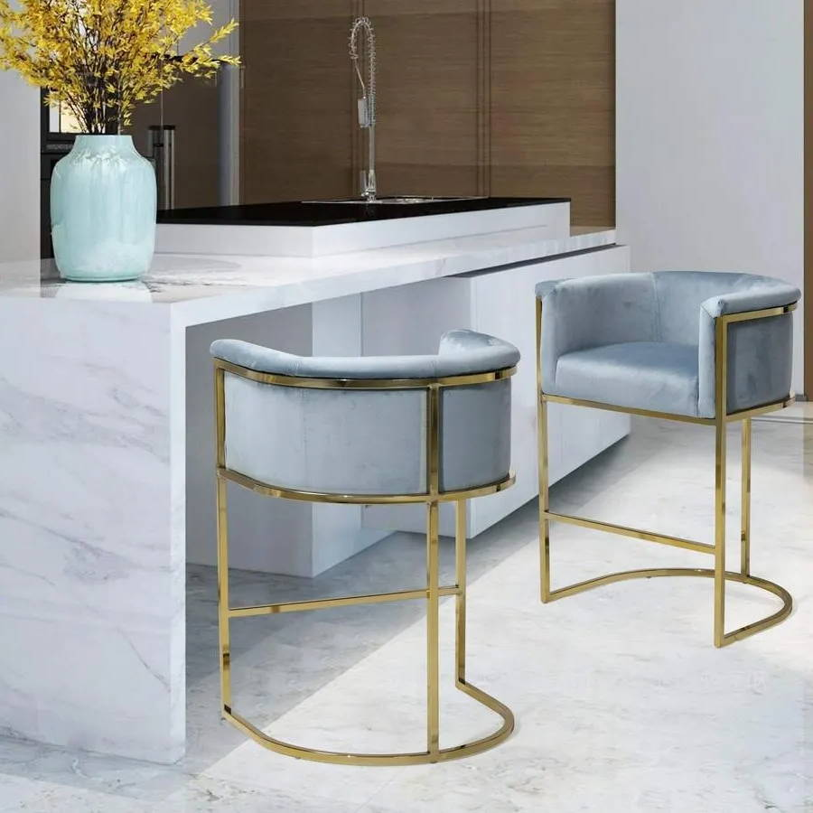 A dining area with two light blue Iconic Home Finley counter stools next to a marble counter top