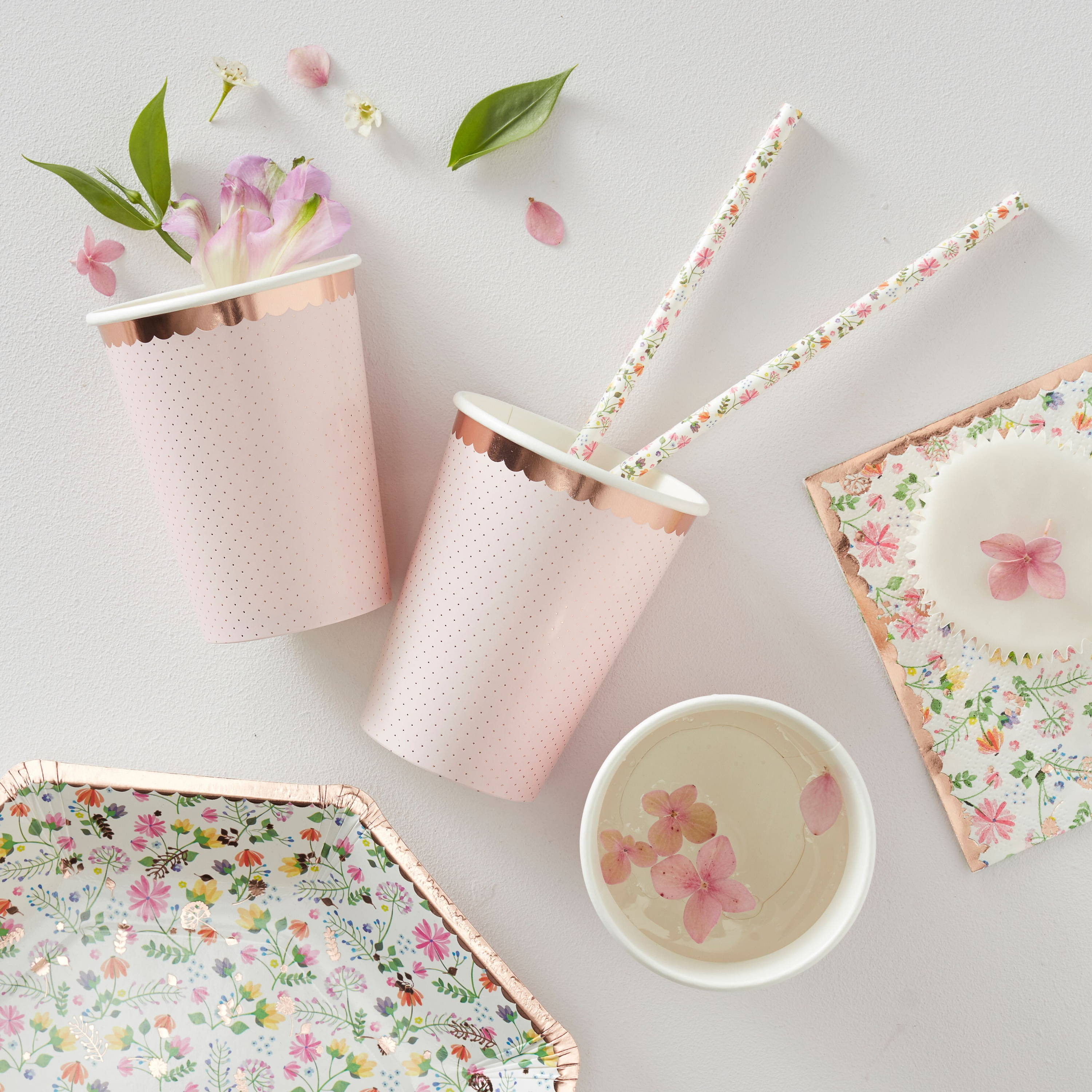 A photo of a classy hen party decor range on a table including pastel pink party cups, ditsy floral party plates, pictured with flowers, rose water and cupcakes on a floral napkin