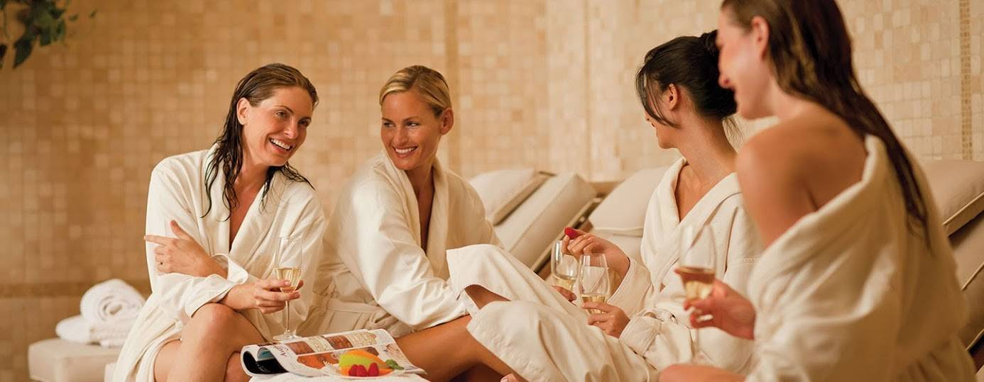 Women drinking champagne in robes