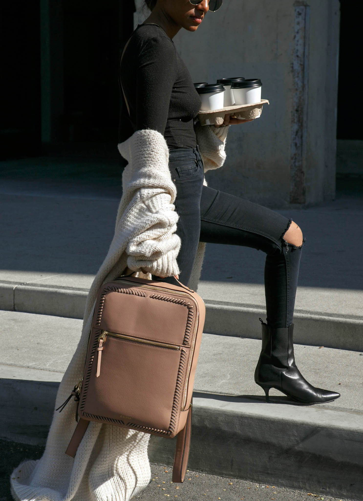 model with CALPAK Kaya laptop backpack in caramel color
