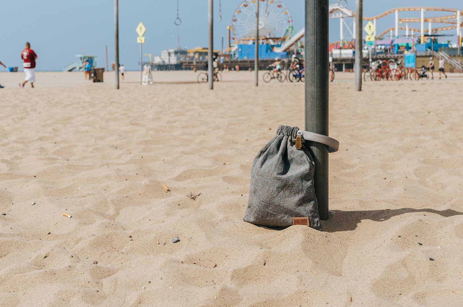 grey anti theft drawstring backpack secured to post at beach