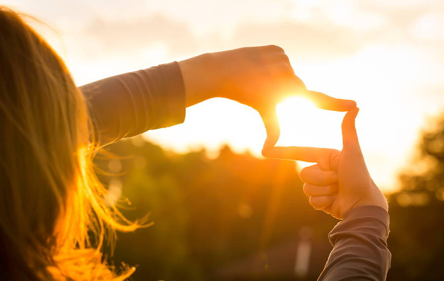 woman holding hands up to sun