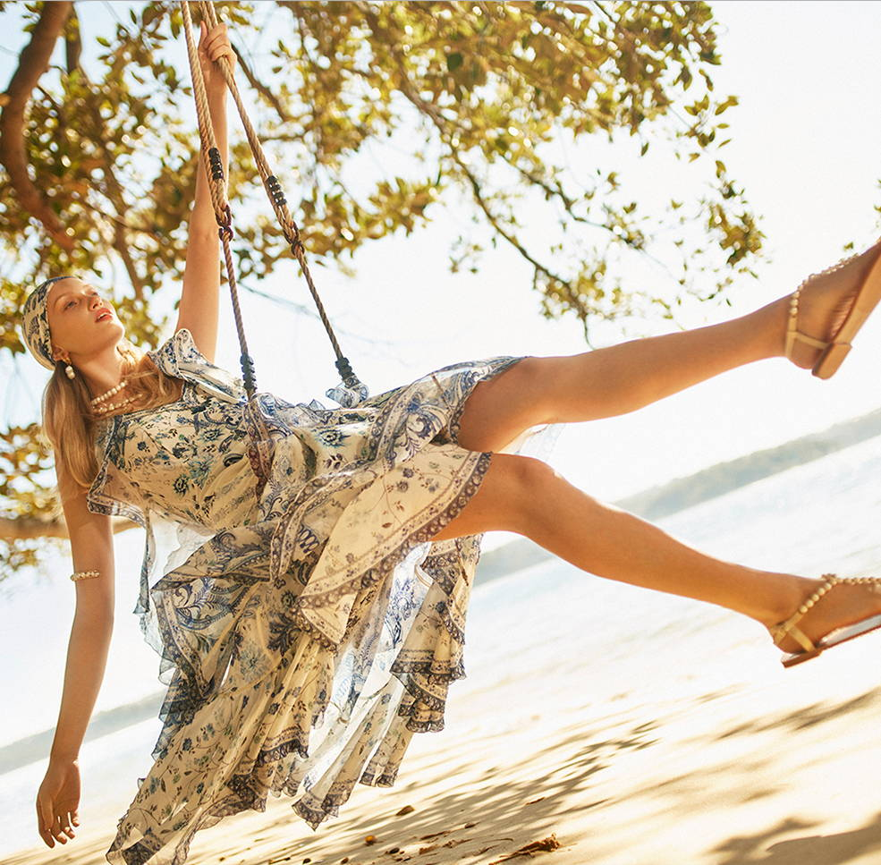 Model on swing at beach wearing CAMILLA blue and white floral print cami, skirt and scarf