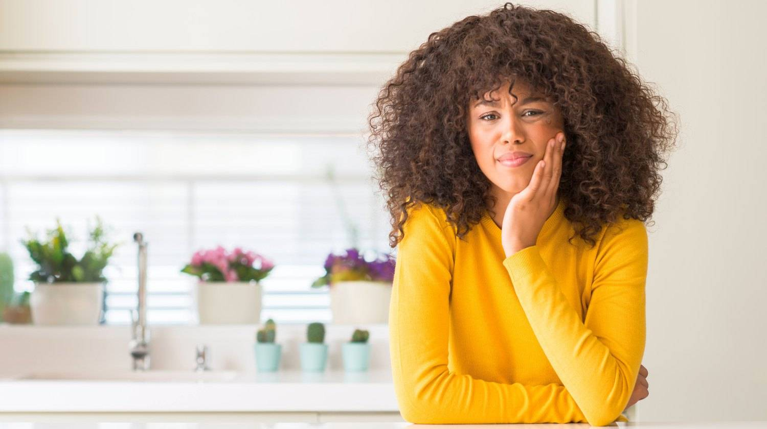 Featured | African american woman wearing yellow sweater at kitchen touching mouth with hand with painful expression | Coconut Oil for Canker Sores - How Does It Work?