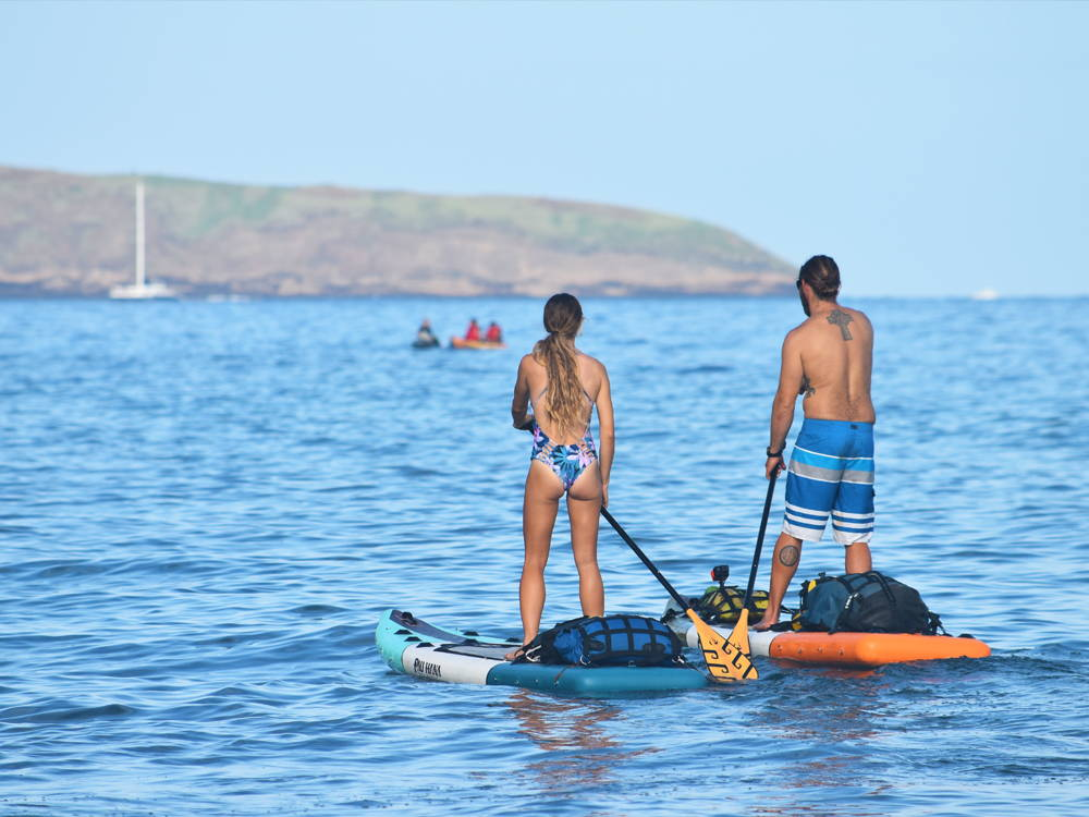a couple paddling on inflatable paddle boards