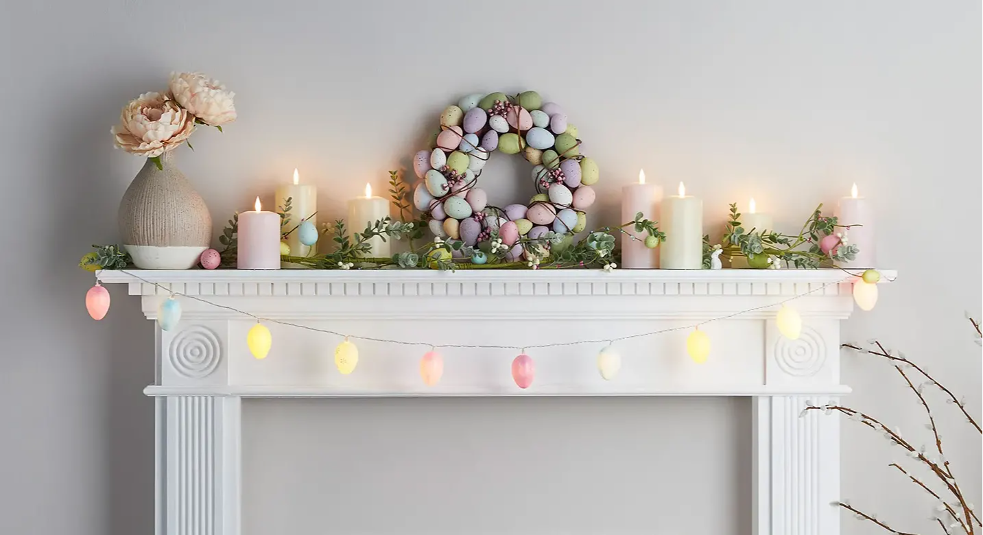 Easter mantel with assortment of pastel and egg TruGlow candles and Easter wreath and garland styled alongside