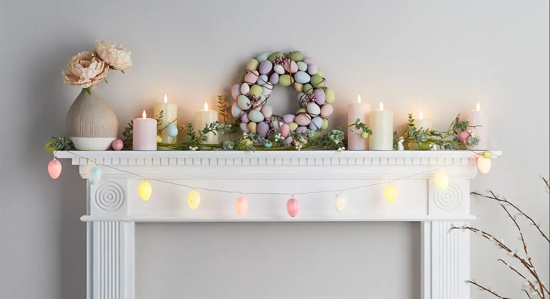Für Ostern dekorierter Kaminsims mit pastellfarbenen TruGlow Kerzen sowie Osterkranz und -girlande