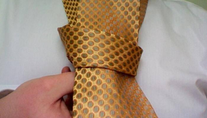 Man tying a half windsor tie knot