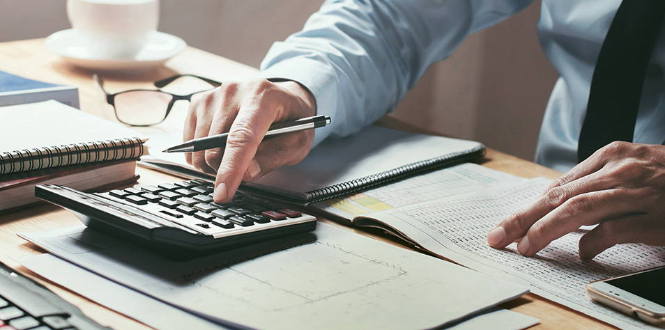 A closeup view of a tax representative typing on his calculator.