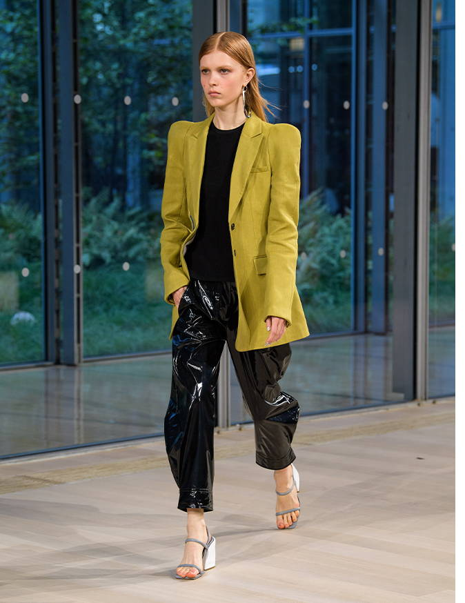 Spring 2020 runway image of model wearing patent pants and a green sculpted blazer.