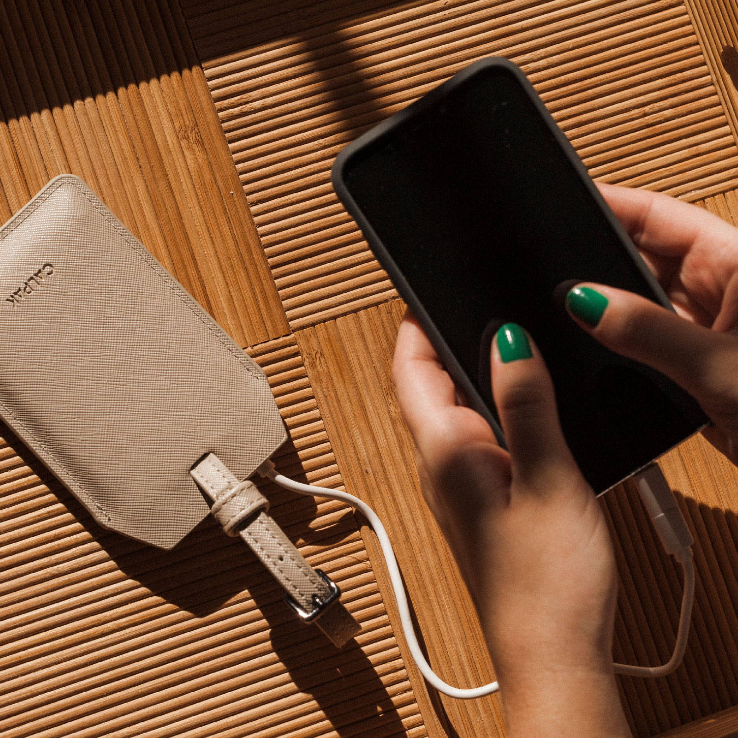 CALPAK Portable Charger with smartphone attached