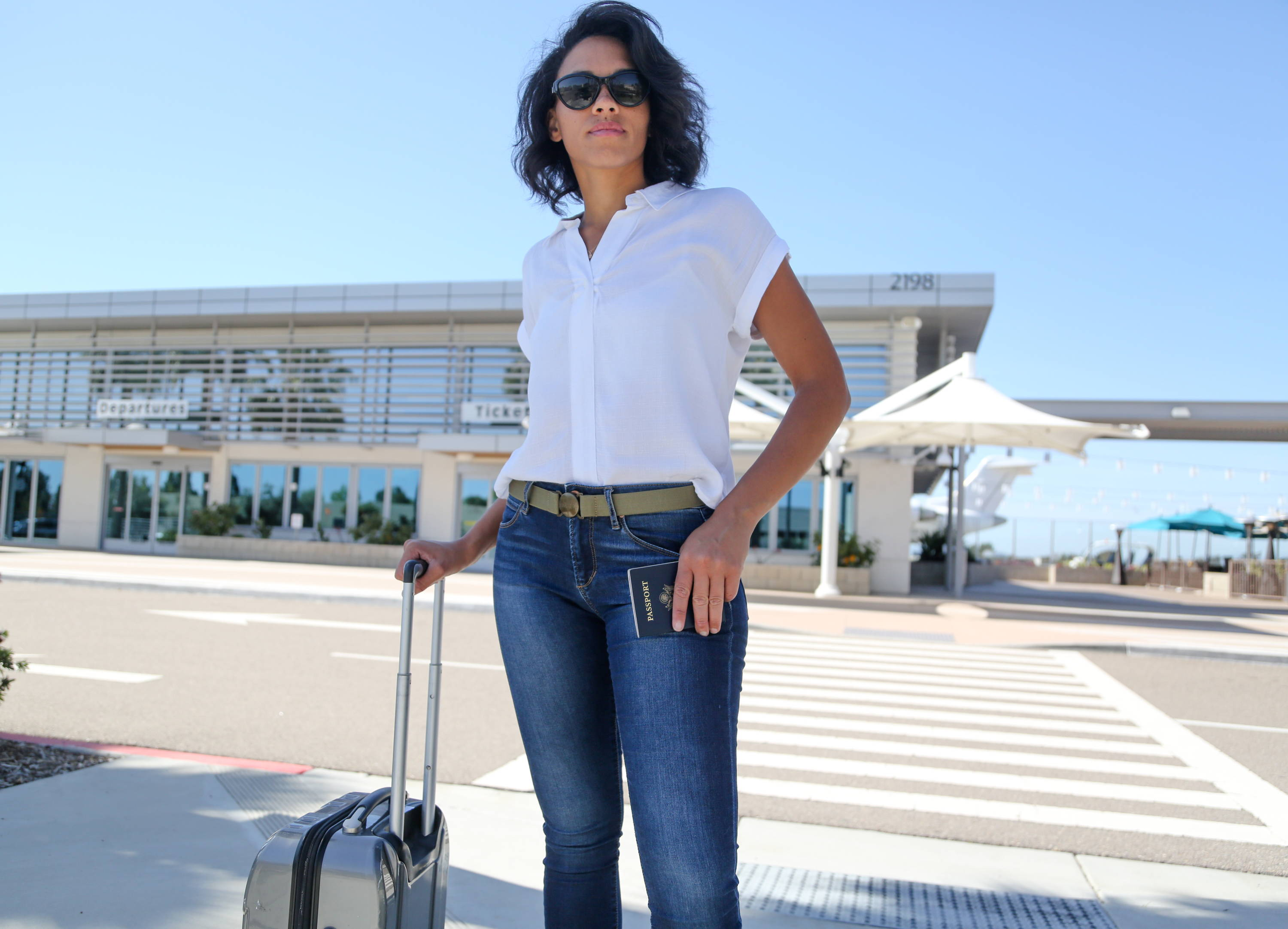 Woman  wearing  a Jelt Original elastic stretch belt in black Granite while traveling through airport  with  suitcase and passport in hand.