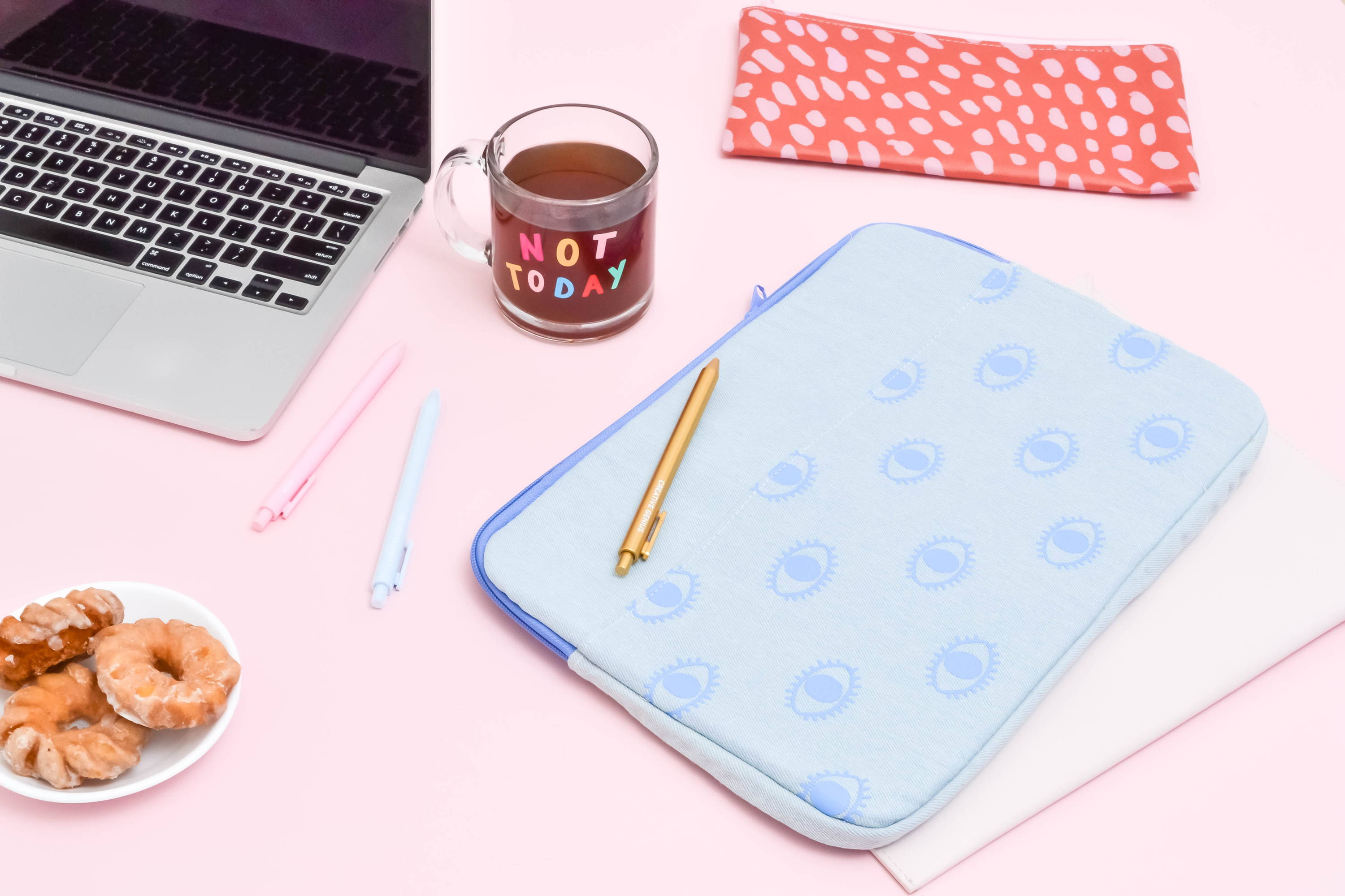cute lifestyle image of a laptop, donuts, blue canvas laptop sleeve with eyeballs, a red vegan leather pouch, and a clear glass mug that says not today in rainbow letters