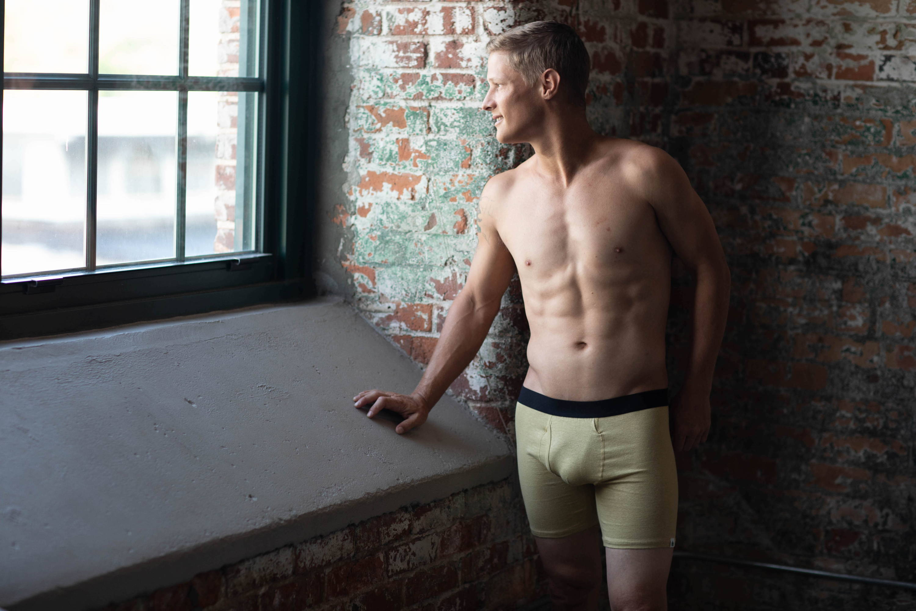 A handsome young man in a brick building looking out of a window while wearing nothing but WAMA hemp boxer briefs.