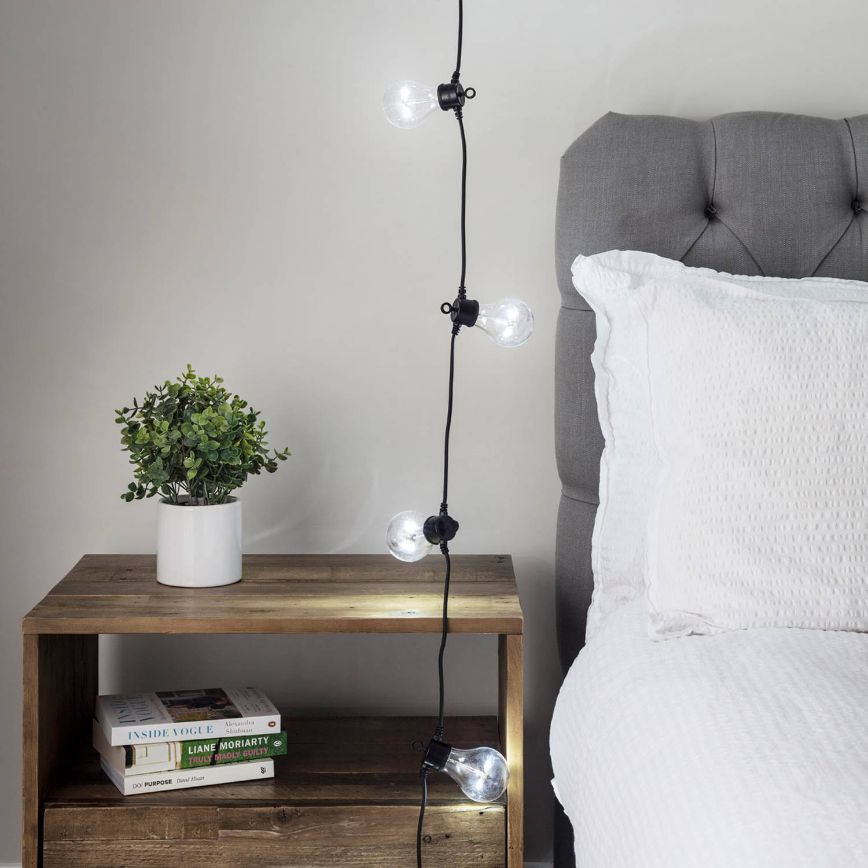 Kaltweiße Party Lichterkette im Schlafzimmer mit kleiner Pflanze und Büchern auf Nachttisch.