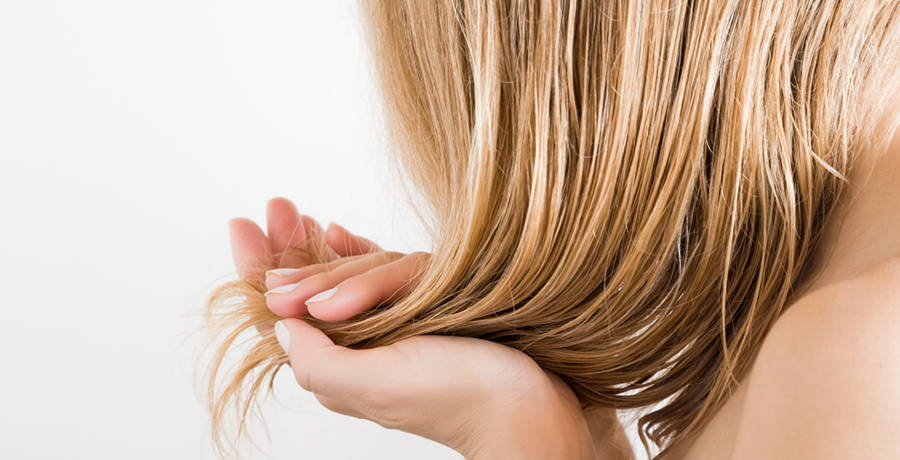 woman adding almond oil to her hair