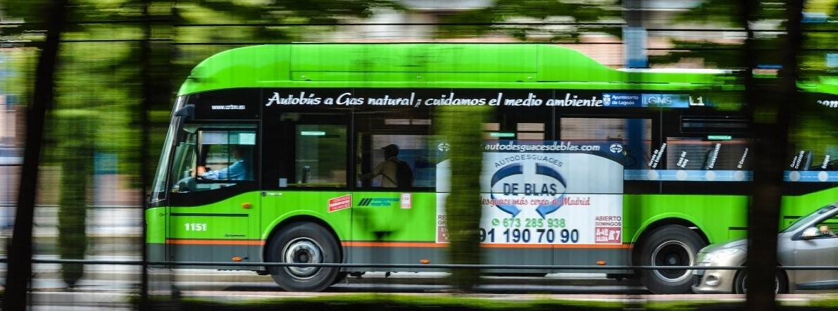 A modern, natural gas powered bus navigates its way through busy city streets
