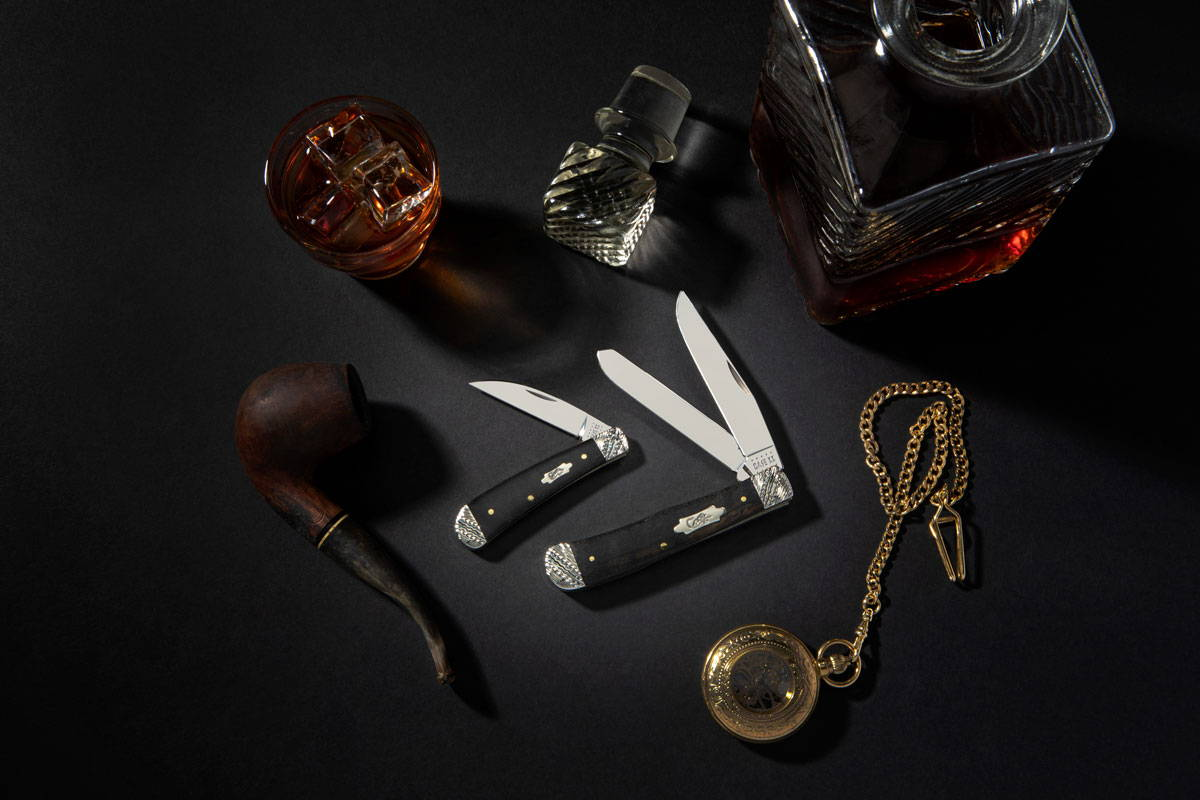 Ebony wood bolster knives surrounded by luxury items.