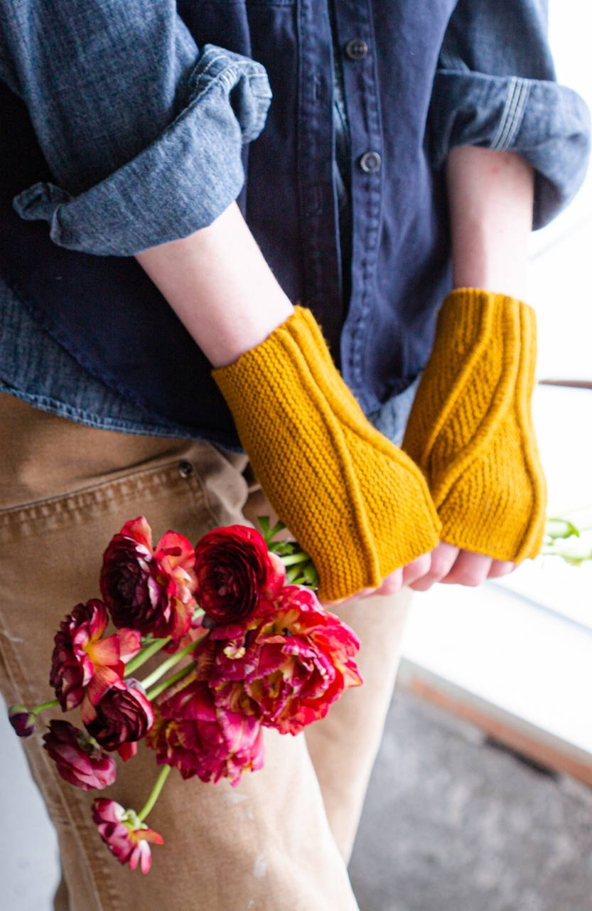 Image of Alyssa modeling Limn mitts holding flowers