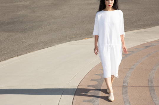 A women in a white dress walking and wearing Vision Quest light colored shoes
