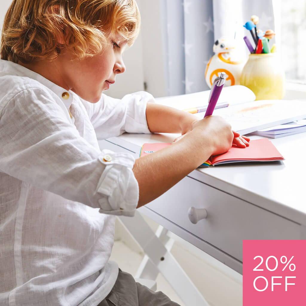 young boy working at white children's desk