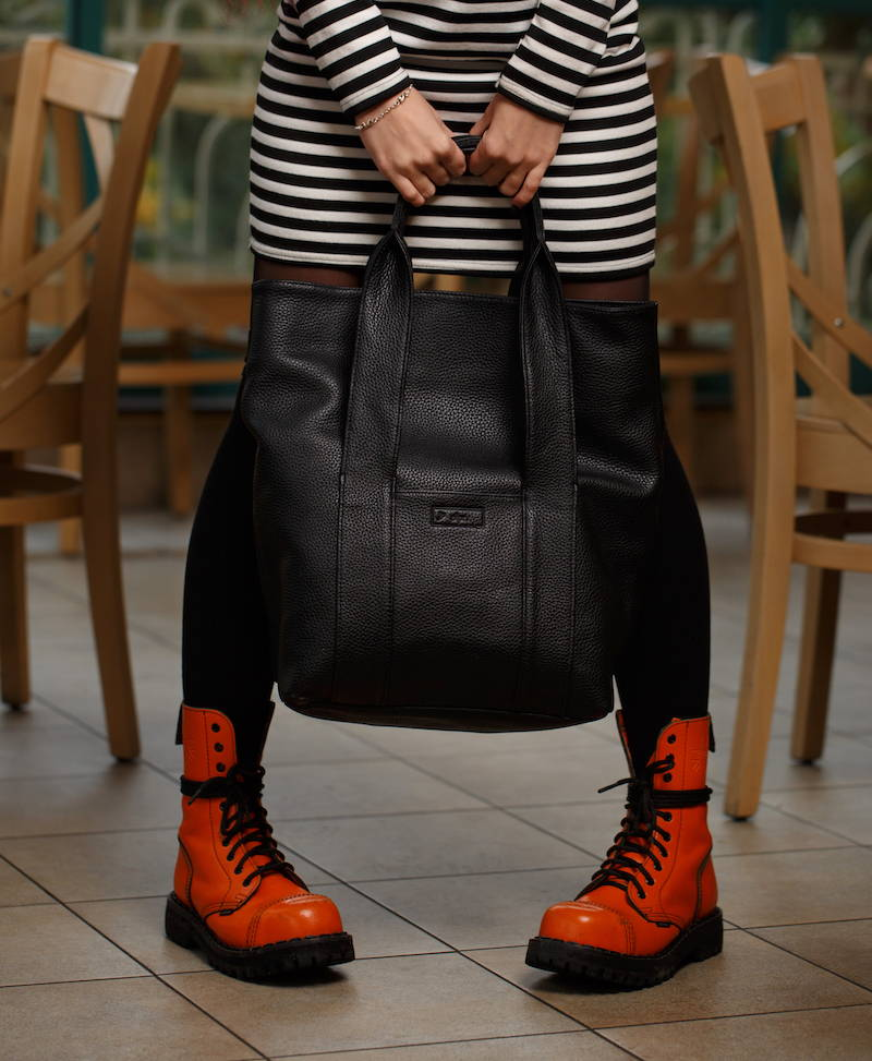 girl holding black leather tote bag
