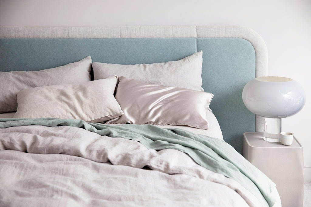 Bed styled with Cultiver linen duvet cover and pillowcases in Smoke Grey and a Sage flat sheet. Also featured is the Foscarini Buds 2 table lamp.