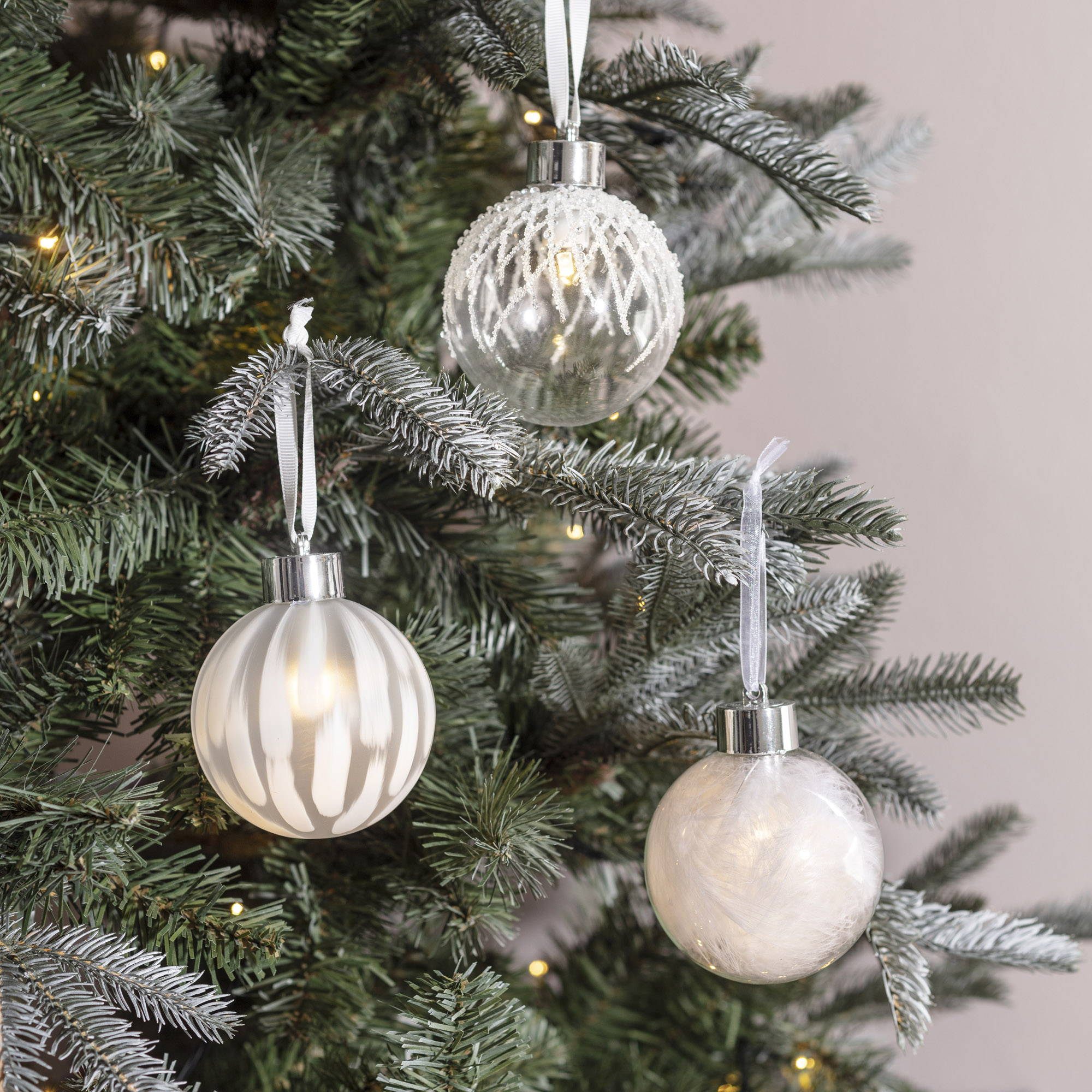 LED White Christmas Baubles hanging as a trio off a frosted Christmas tree