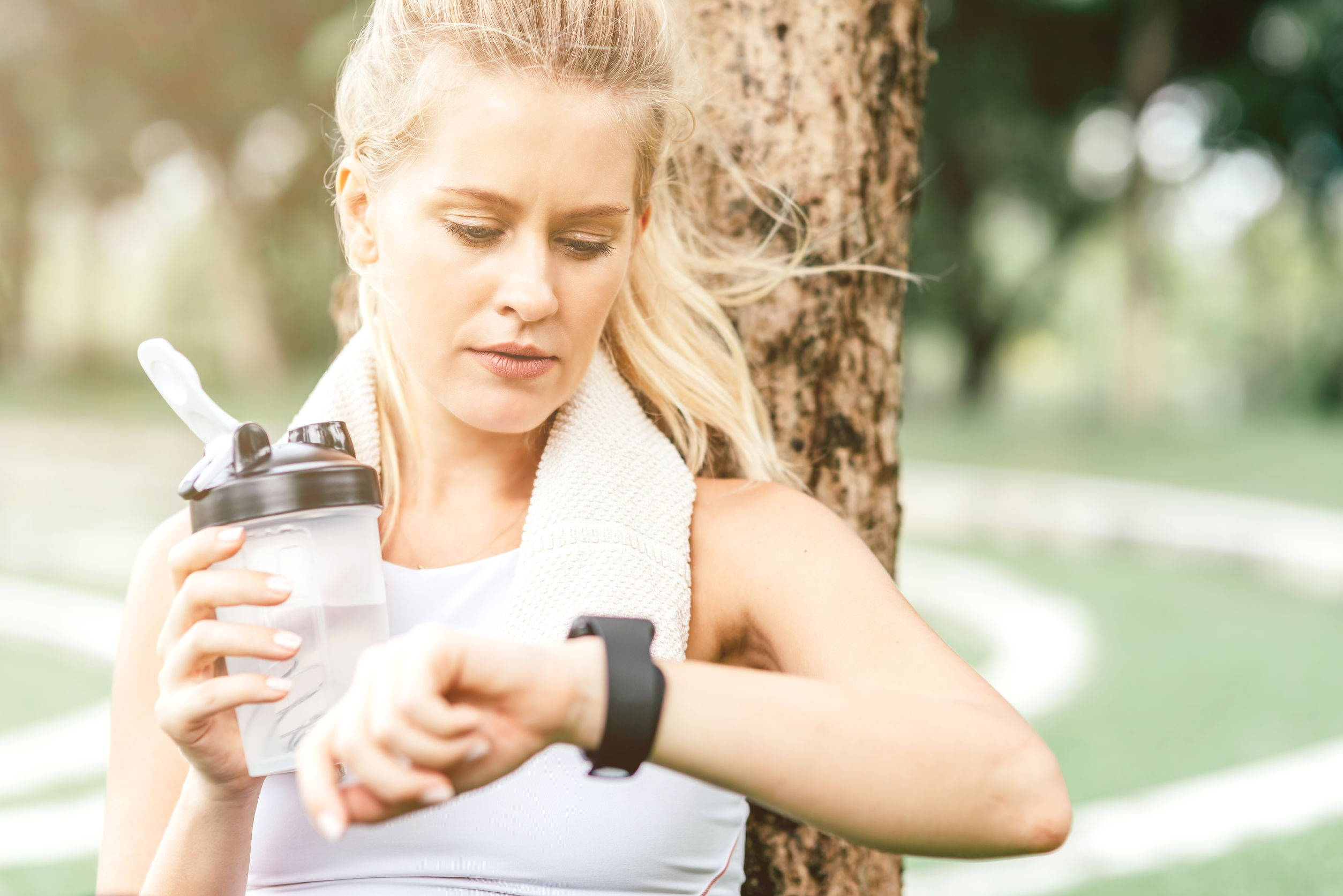A woman checks her watch as she drinks her pre-workout drink.