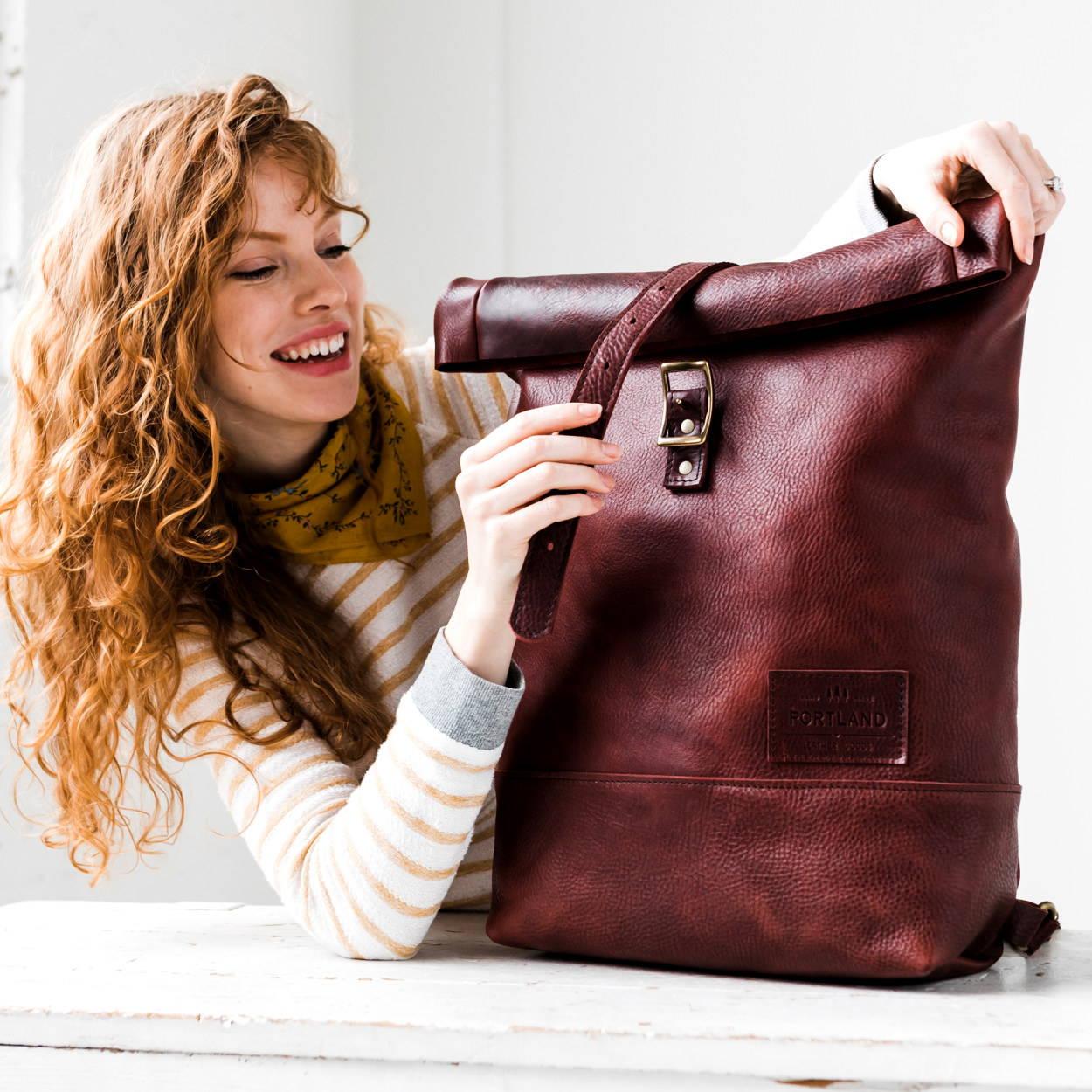 smiling model unbuckling oxblood rolltop backpack