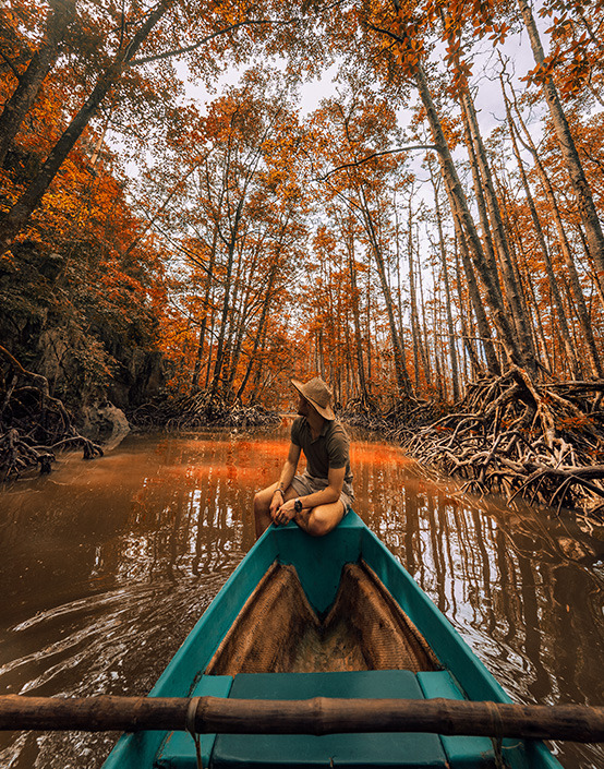 man in boat on river in forest