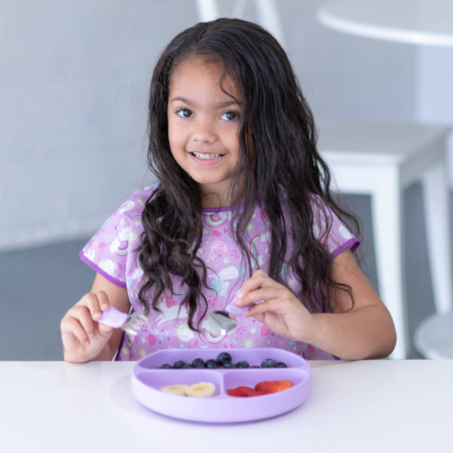 kid wearing bib eating from purple suction dish with utensils