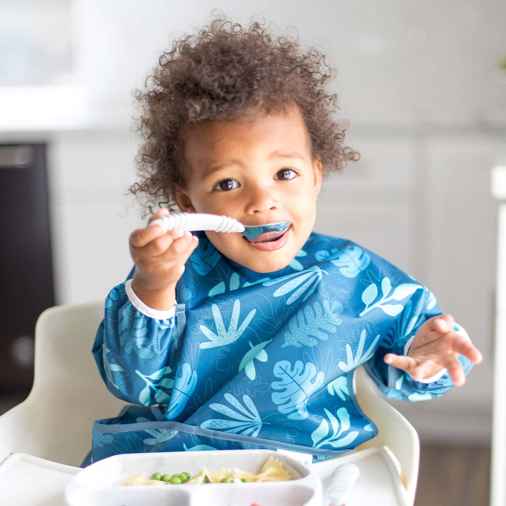 toddler feeding himself out of a bumkins grip dish 3-section with a bumkins fork