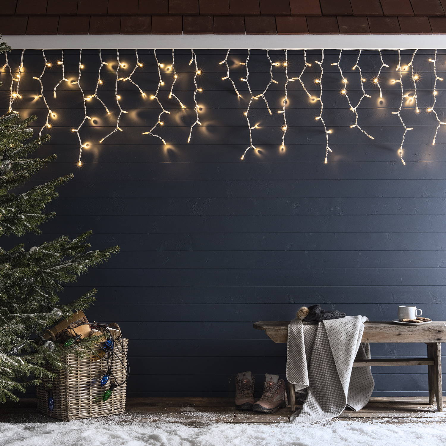 Warm white icicle lights hanging from a snowy winter cabin