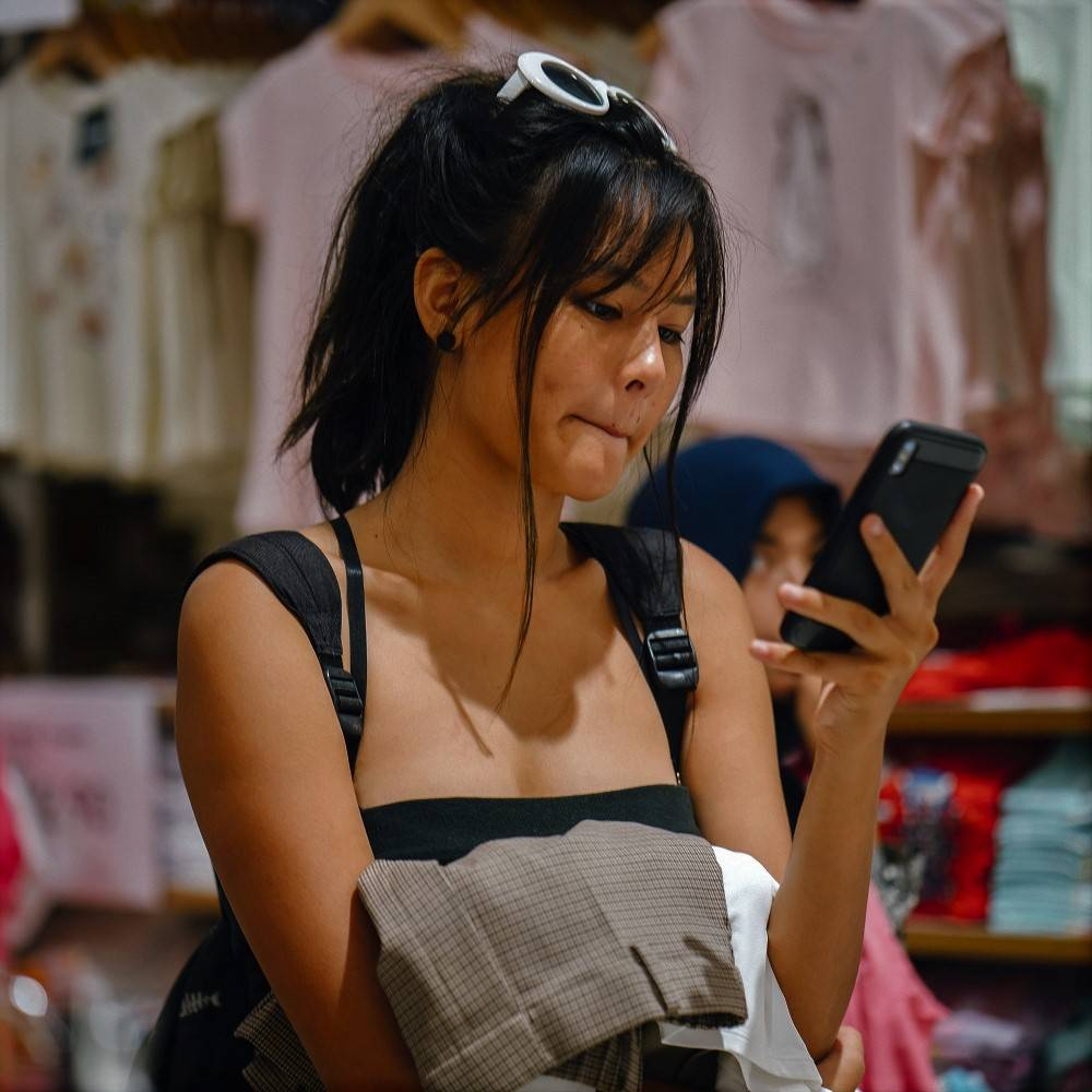 A lady using her phone while clothes shopping