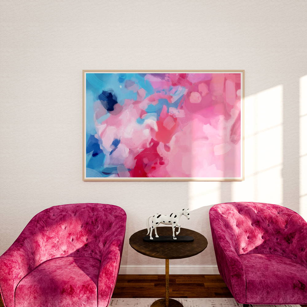 Large bright pink and blue abstract art print- landscape wall art in sitting area with pink chairs.
