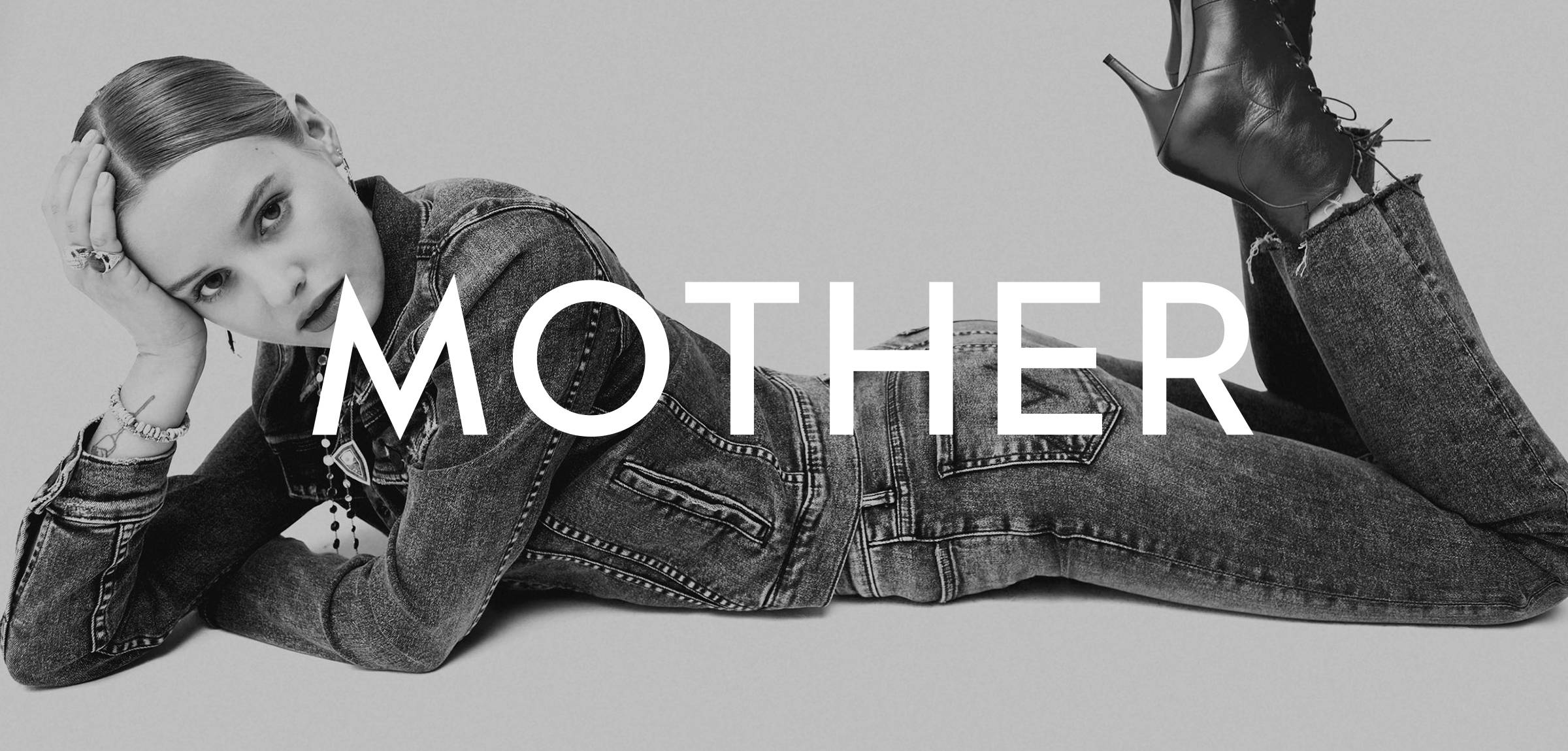 Woman laying down dressed in denim with MOTHER logo overlay