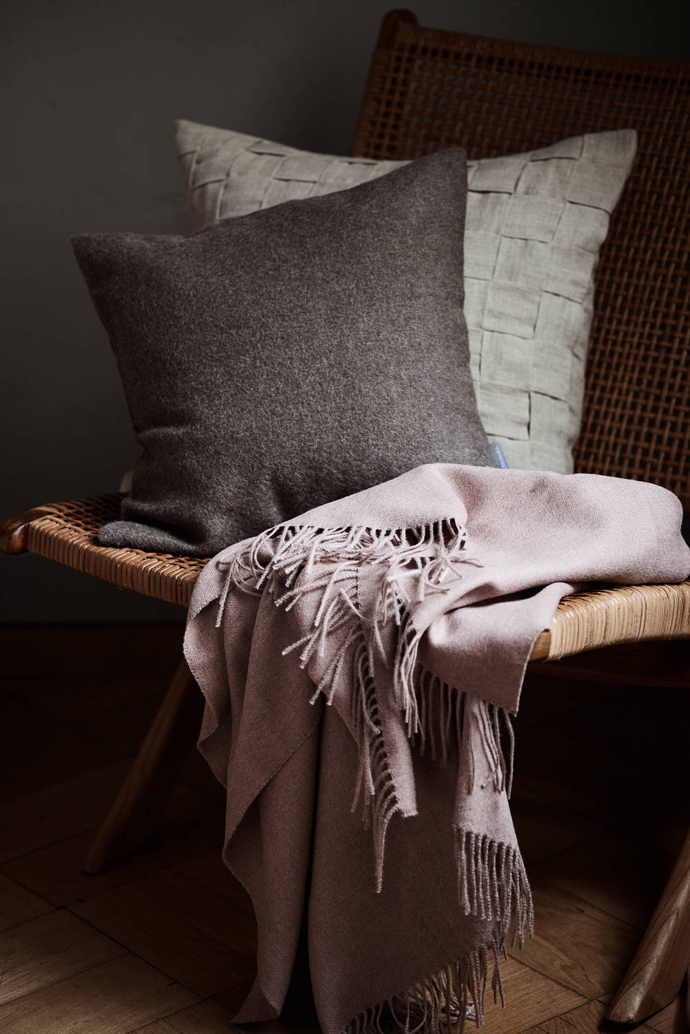 Rattan woven armchair with layered Hygge cushions and pink wool blanket