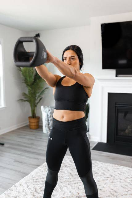 A woman performing a high-intensity Tabata workout in her home gym.