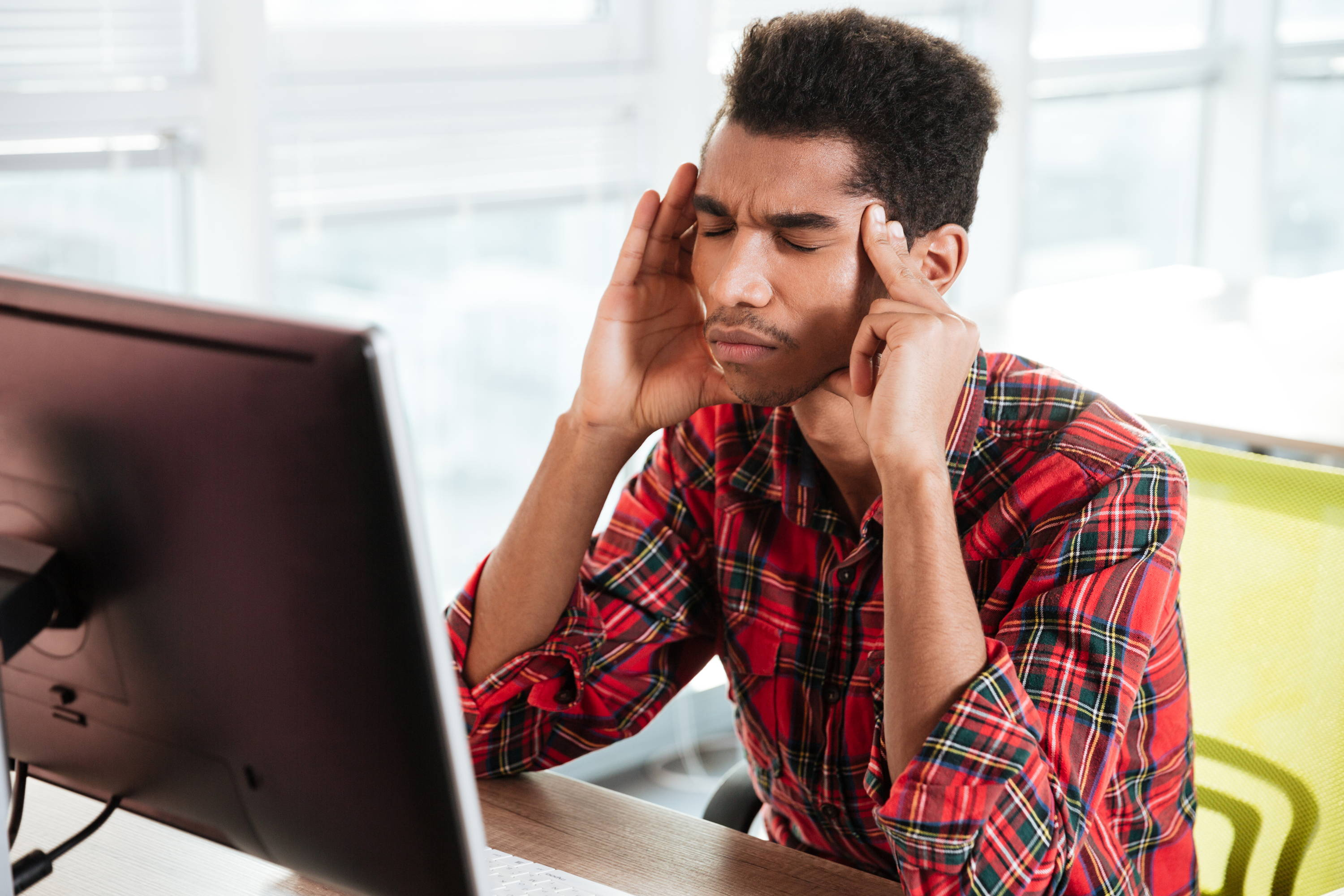 Man holing his temples wining with pain with his eyes closed in front of a computer.