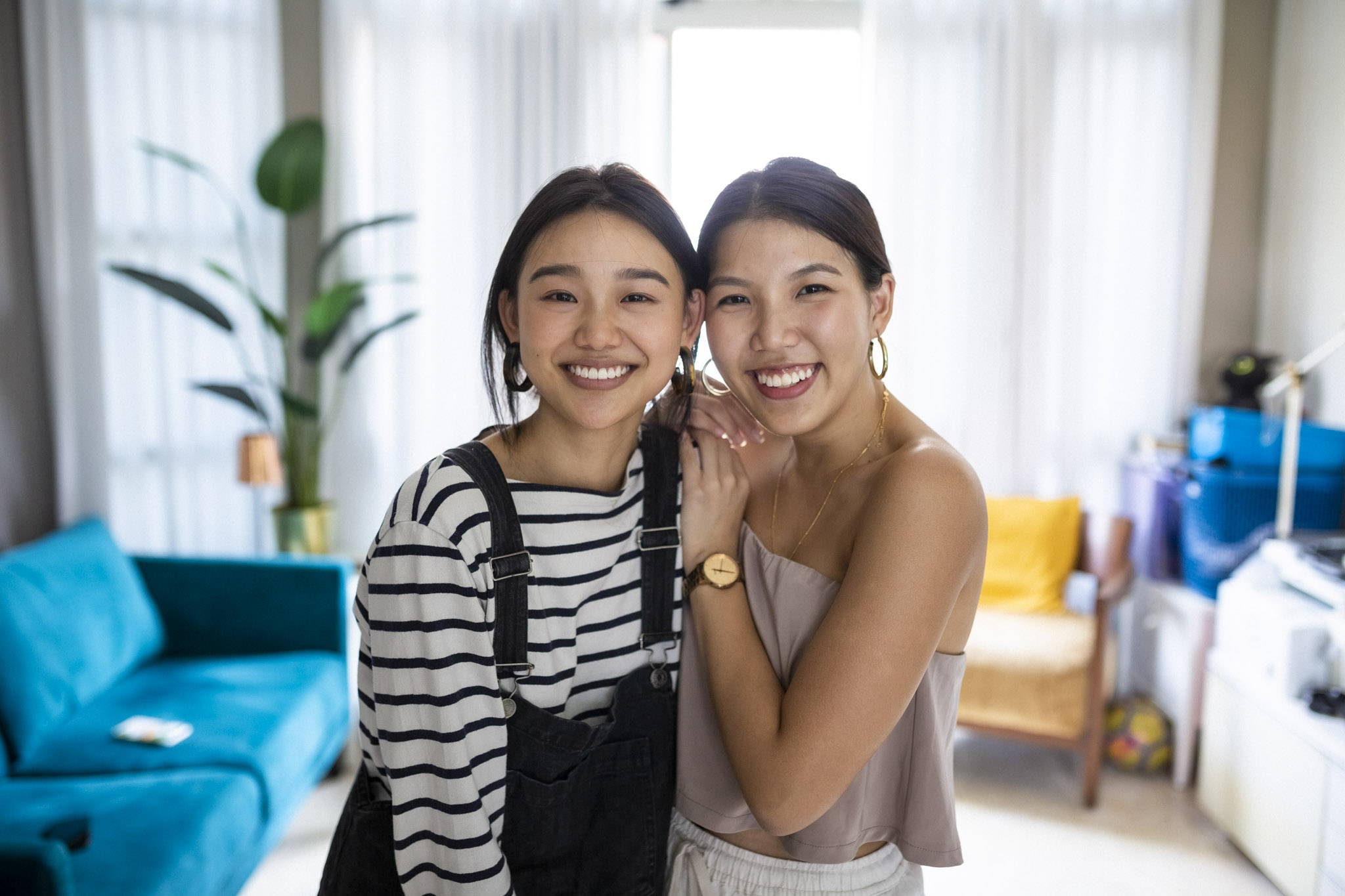Serena and Gabriela from Oh, Culture in their home smiling. Serena is wearing a striped long-sleeved shirt. Gabriela is wearing a nude crop top.