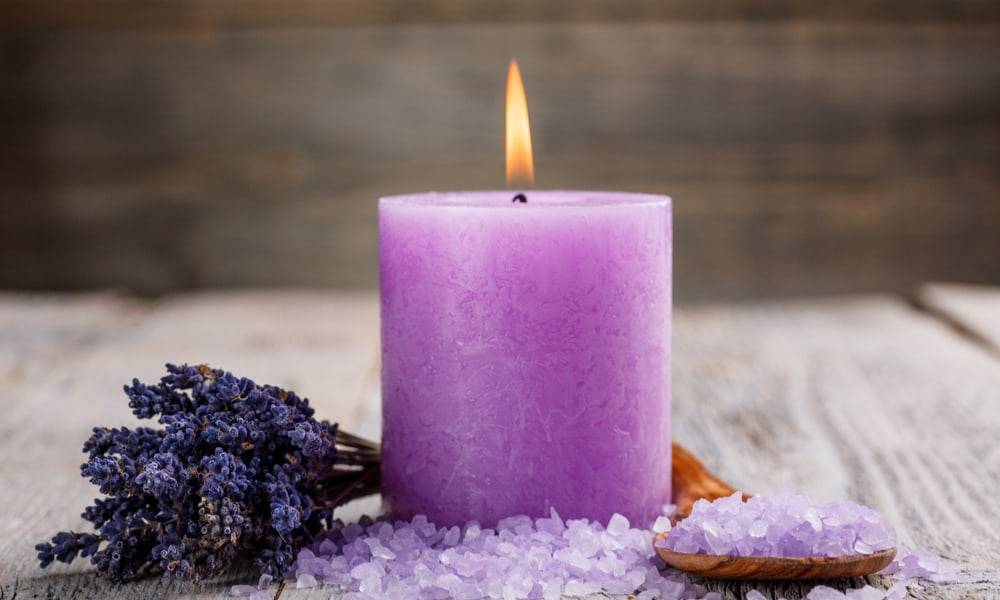 purple candle lit on wood table with salts and lavender sprigs next to it