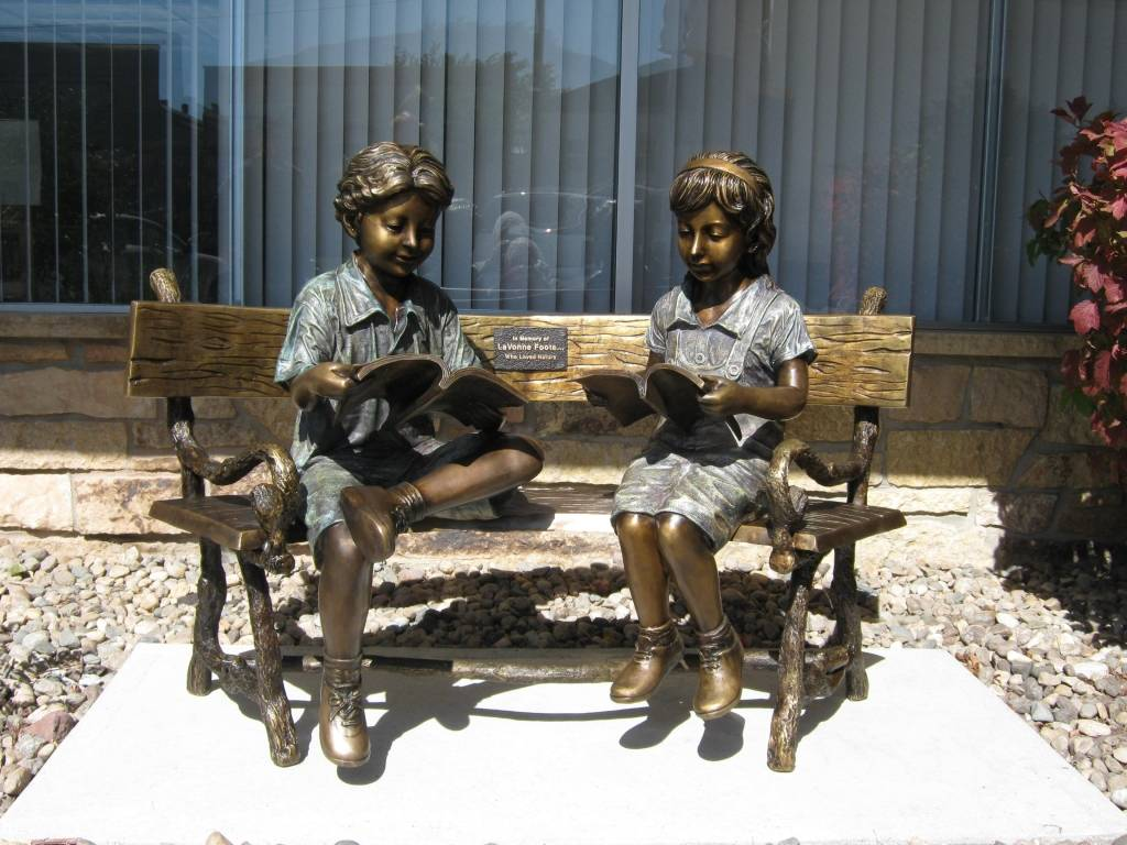 Bronze statue of a boy and girl sitting on a bench reading a book