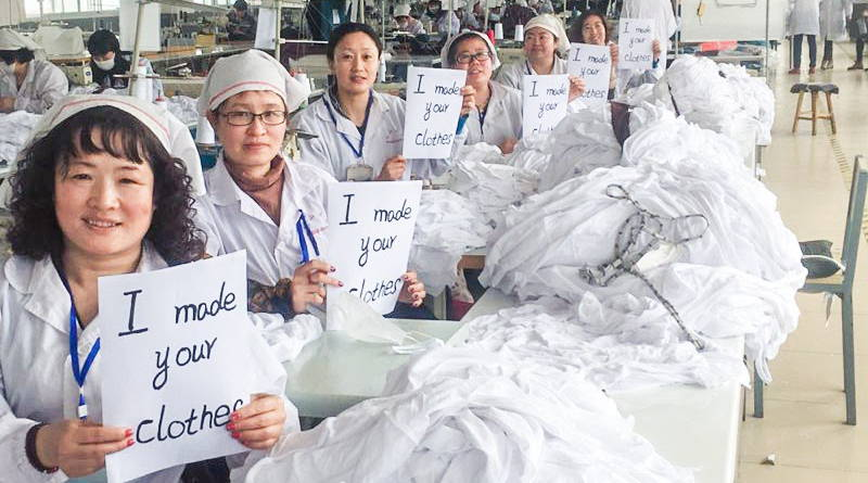 "Employees at WAMA's hemp underwear factory in China smile and proudly hold signs saying ""I made your clothes"" at their work stations."
